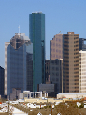 The dense group of modern skyscrapers stand behind a residential area in downtown Houston, Texas, USA.