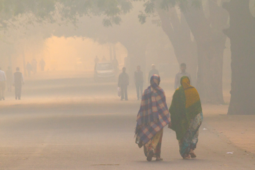 Pedestrians in India surrounded by thick air pollution