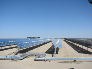 Figure 3. Part of the 50-MW concentrated solar power (CSP) plant at the Shagaya Renewable Energy Park in western Kuwait, with the new KISR research facility and the wind turbines in the background.
