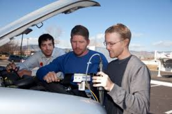 NCAR researchers Sheldon Drobot, Michael Chapman, and Brice Lambi install a vehicular weather sensor.